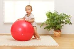 De jongen van de baby met grote rode bal Stock Afbeelding
