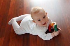 De jongen van de baby met zijn eerste speelgoed Stock Afbeelding