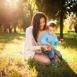 De jongen van de baby in het park met zijn mum Stock Fotografie