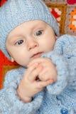 De jongen van de baby onderzoekt zijn handen Stock Foto's