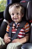 De jongen van de baby in zijn de autozetel van de kindveiligheid Stock Foto