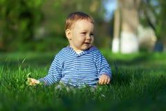 De jongen van de baby zit op groen gras, de lentegazon Stock Foto