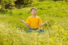 De jongen van de blondetiener in een lotusbloempositie die, meditatie op Na mediteren Royalty-vrije Stock Fotografie