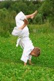 De jongen van de karate doet handstand op gazon royalty-vrije stock foto's