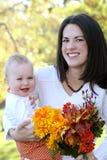 De Jongen van de moeder en van de Baby met Bloemen - het Thema van de Daling Stock Afbeelding