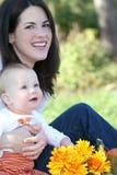 De Jongen van de moeder en van de Baby met Bloemen - het Thema van de Daling Royalty-vrije Stock Afbeeldingen