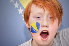 De jongen van de roodharigeventilator met de vlag van Bosnië-Herzegovina schilderde op zijn gezicht Stock Fotografie