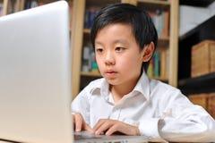 De jongen van de school in wit overhemd voor laptop computer Stock Afbeeldingen