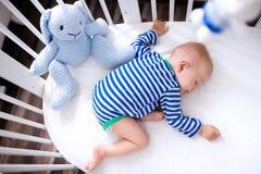 De jongen van de slaapbaby in witte voederbak Stock Fotografie
