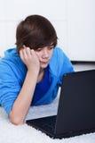 De jongen van de tiener met laptop stock fotografie