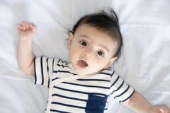 De jongen van de verrassingsbaby in de voederbak stock afbeeldingen