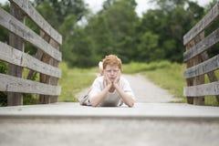 De jongen van het land op een houten omheining Stock Afbeeldingen