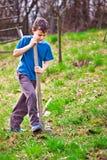 De jongen van het landbouwbedrijf het graven met een schop Stock Fotografie