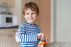 De jongen van het schooljonge geitje het spelen met veel klein kleurrijk plastic blok stock fotografie