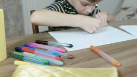 De jongen van 7 jaar in een gestreepte t-shirt trekt zelfs lijnen op papier met een potlood en een heerser blur stock video