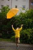 De jongen van 8-9 jaar in een heldere gele regenjas probeert om de het vertrekken paraplu te vangen Stock Afbeelding