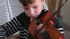 De jongen van 8 jaar speelt viool stock video