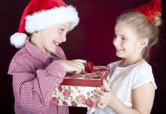 De jongen van Kerstmis aanwezige geven aan glimlachend meisje Royalty-vrije Stock Afbeeldingen
