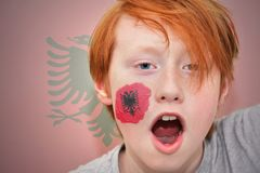 De jongen van de roodharigeventilator met Albanese vlag schilderde op zijn gezicht stock foto