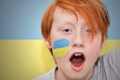De jongen van de roodharigeventilator met Oekraïense vlag schilderde op zijn gezicht royalty-vrije stock afbeelding