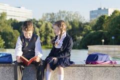 De jongen van de school leest het boek het meisje zijn naam, de houding van de studenten vraagt stock fotografie