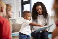 De jongen van de zuigelingsschool het richten in een boek door de vrouwelijke leraar wordt gehouden, die met jonge geitjes op sto stock foto's