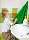 De jongen veegt handen af een badstofhanddoek na was Royalty-vrije Stock Afbeeldingen
