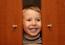 De jongen verbergt in een garderobe Royalty-vrije Stock Foto