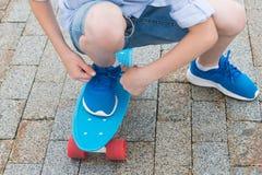 De jongen verbindt een koord op een blauwe tennisschoen terwijl status op een sportenraad royalty-vrije stock foto