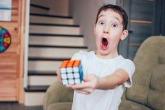 De jongen is verrast en blij dat hij volledig de kubus van Rubik thuis heeft verzameld stock foto