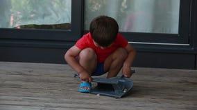 De jongen verzamelt het huisvuil in een lepel stock video