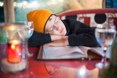 De jongen viel in slaap bij een lijst in een koffie stock afbeelding