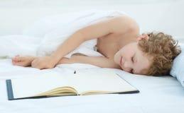 De jongen viel in slaap op de ingangen in het notitieboekje Gezond slaapconcept Stock Afbeelding