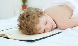 De jongen viel in slaap op de ingangen in het notitieboekje Gezond slaapconcept Stock Foto