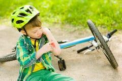 De jongen viel van de fiets in een park stock fotografie