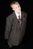De jongen in volwassene rangschikte kostuum Stock Foto