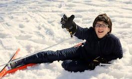 De jongen vraagt om hulp na de daling op skis Stock Foto's