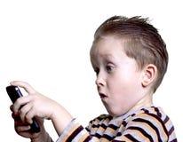 De jongen was verrast om in de telefoon te kijken Stock Fotografie