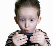 De jongen was verrast om in de telefoon te kijken Royalty-vrije Stock Foto