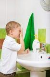 De jongen wast het gezicht Stock Foto