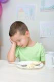 De jongen wil geen maaltijd eten stock fotografie