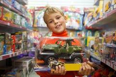 De jongen in winkel met de stuk speelgoed machine in handen Stock Fotografie