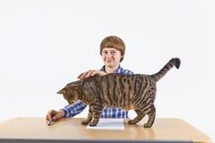 De jongen wordt gestoord door zijn gestreepte katkat terwijl het doen van zijn thuiswerk Royalty-vrije Stock Foto