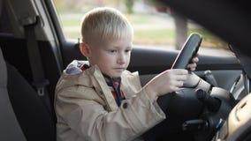 De jongen zat in de bestuurderszitplaats in de auto stock footage