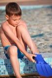 De jongen zet op flippersongrens van pool royalty-vrije stock afbeeldingen