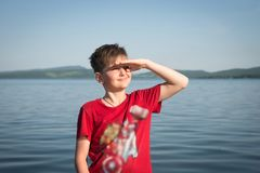 De jongen zijn hand beschermt hij ogen tegen de zon op de achtergrond van het meer op een zonnige dag stock foto