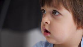 De jongen zit bij een groot venster in de winter en het golven stock video