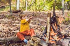 De jongen zit bij de kampbrand stock afbeelding