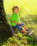 De jongen zit dichtbij boom Royalty-vrije Stock Foto's