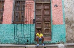 De jongen zit in dooray van zijn huis in Havana, Cuba Stock Afbeeldingen
